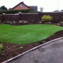 A final shot of the newly layed artificial grass complimented with willow screening in the newly landscaped garden