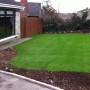 Artificial grass surrounded by newly landscaped gardens